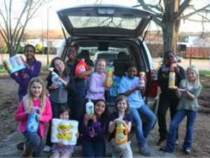 Girl Scouts with cleaning supplies and toiletries they collected to donate HopeMatch families